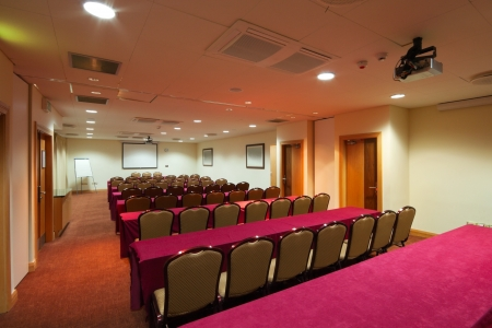 projection: Conference room Interior with tables raw of chairs, screen and projector Stock Photo
