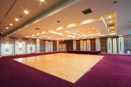 Huge Hall interior with wooden dance floor,  red carpet and ceiling with lights in Hotel
