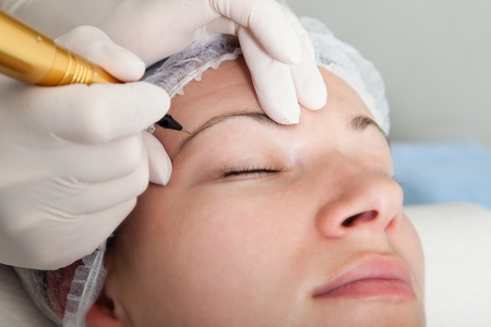 cosmetologist: Cosmetologist making permanent makeup Stock Photo