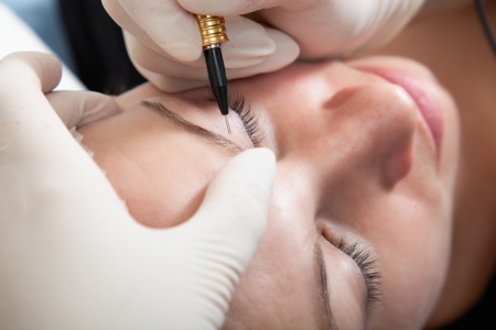 Cosmetologist making permanent makeup photo