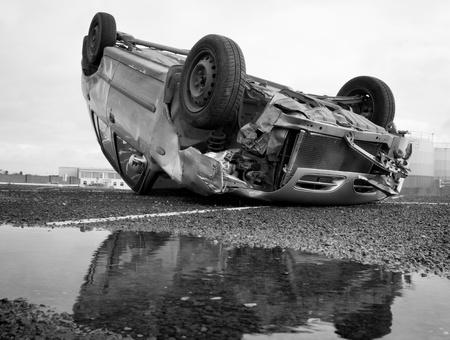 coche convertido al revés después de la colisión de la carretera y la reflexión en el agua