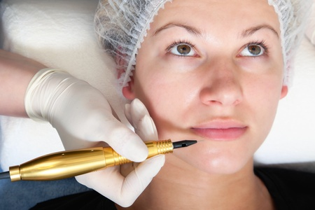 Cosmetologist making permanent makeup on womans face photo