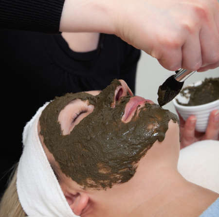 cosmetologist: cosmetologist applying seaweed beauty mask at womans face