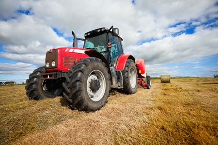 huge tractor collecting haystack in the field in a nice blue sunny day Archivio Fotografico