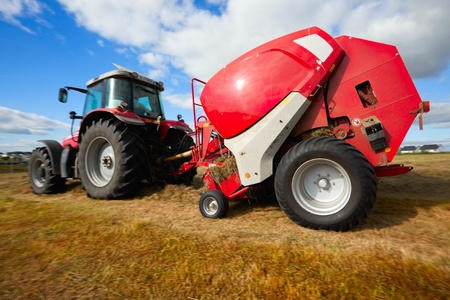 huge tractor collecting haystack in the field in a nice blue sunny day photo