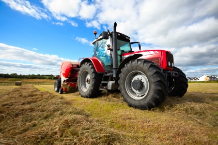 agriculture machinery: huge tractor collecting haystack in the field in a nice blue sunny day Stock Photo