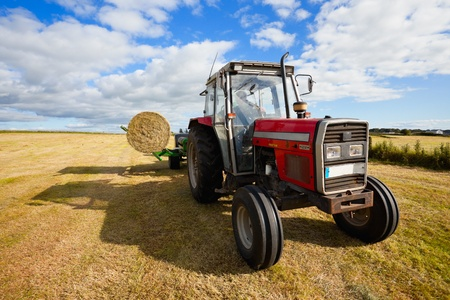 huge tractor collecting a roll of haystack in the field at nice blue sunny day photo