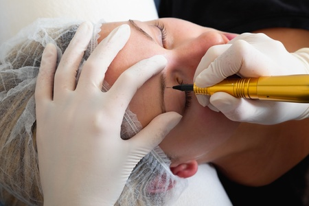 cejas: Cosmet�loga haciendo maquillaje permanente en el rostro de la mujer
