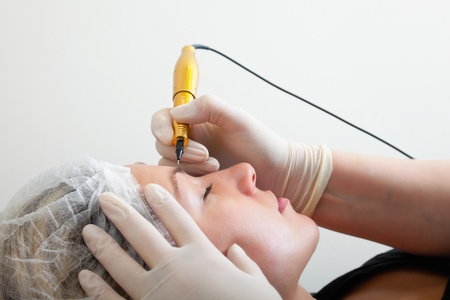 Cosmetologist making permanent makeup on womans face Stock Photo