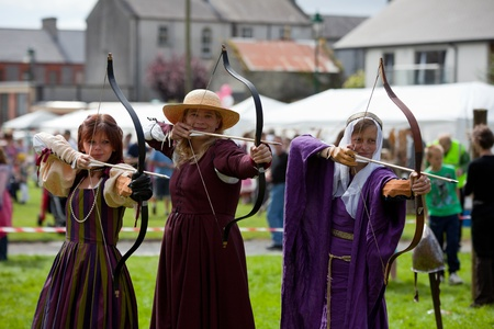 ATHENRY, IRELAND - AUGUST 21: Donna, Claire and Katia  from Eireann Edge displays Archery at annual National Walled Towns Day  on August 21, 2011 in Athenry, Ireland.