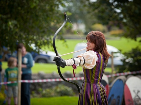 active arrow: ATHENRY, IRELAND - AUGUST 21: Donna from Eireann Edge displays Archery at annual National Walled Towns Day  on August 21, 2011 in Athenry, Ireland.