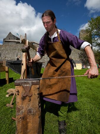 ATHENRY, IRELAND - AUGUST 21: Charlie Gallagher from Eireann Edge displays blacksmithing at annual National Walled Towns Day  on August 21, 2011 in Athenry, Ireland.