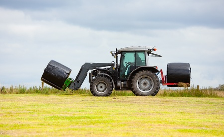 tractor collecting a roll haystack in the field at nice blue sunny day photo