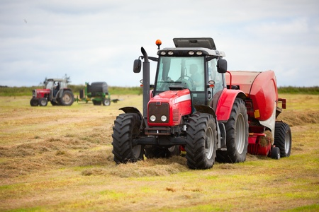huge tractor collecting haystack in the field in a nice blue stock