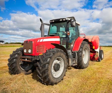 traktor: riesigen Traktor Sammeln Heuhaufen auf dem Gebiet an sch�nen blauen sonnigen Tag