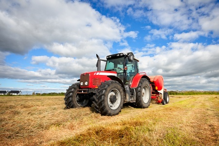 huge tractor collecting haystack in the field at nice blue sunny day photo