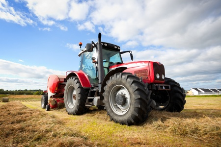 farm tractor: huge tractor collecting haystack in the field at nice blue sunny day