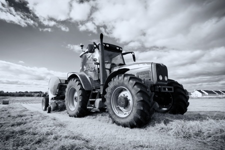 huge tractor collecting haystack in the field at nice day, monochromatic photo