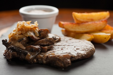 Dry Aged Hereford Rib-Eye Steak with Caramelised onions, Mixed Forrest Mushrooms, Pepper Sauce photo
