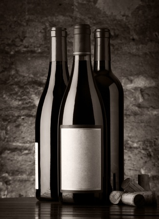 Bottles of red wine with corks and old brick wall background photo