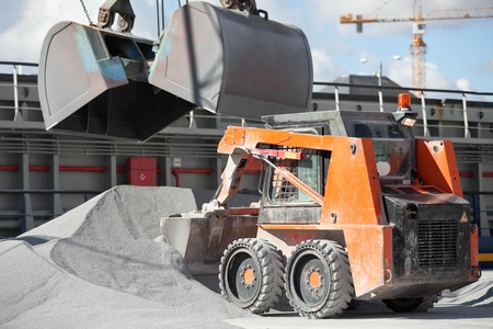 Crane loading cargo ship with gravel assisted by bobcat Stock Photo - 15420403