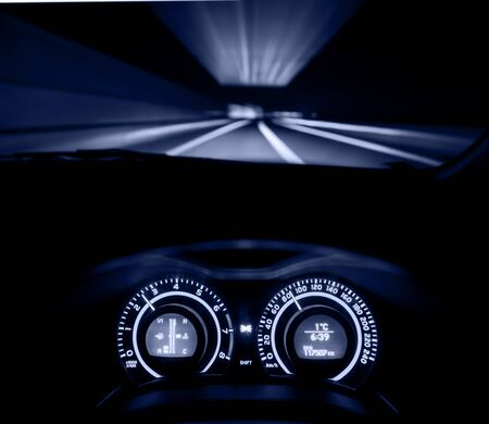 windscreen: Driver view at speeding car  dashboard and motorway  at night, Monochromatic Stock Photo