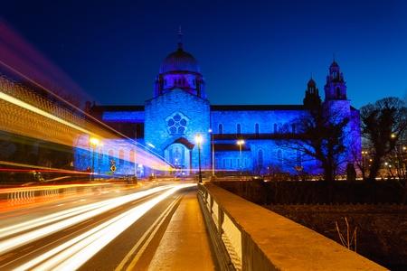 trails of lights: Cattedrale di Galway illuminato blu di notte e auto luci sentieri Archivio Fotografico