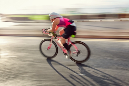 bicycle helmet: Female athlet riding bicycle at sunny day on coastal road, blurred motion