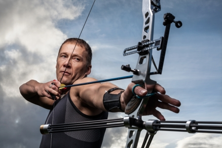 Tough man with bow and arrows, close up with cloudy sky at background Stock Photo