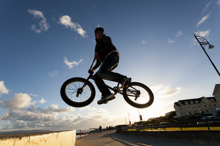 acrobatic: Young man performs BMX stunts during sunset at the street  Stock Photo