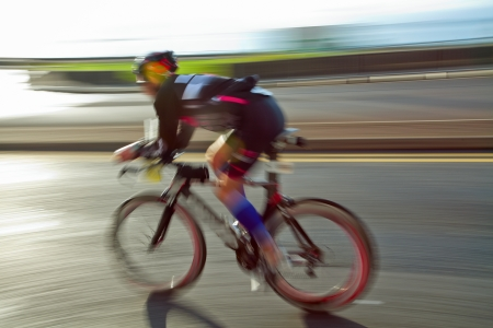 Athlete riding bicycle at sunny day on coastal road, blurred motion