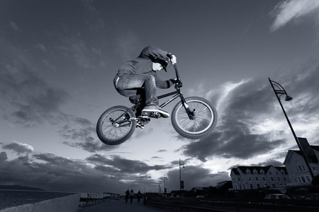 stunts: Young man performs BMX stunts during sunset at the street  Monochromatic