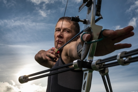 Tough man with bow and arrows, close up with cloudy sky at\ background.