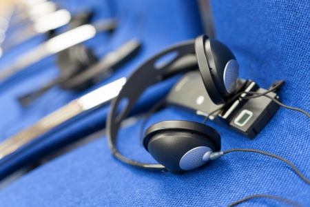 wireless multi language headphones set on the chairs in conference room