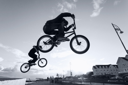 people in action: Two Young men performs BMX stunts during sunset at the street. Monochromatic