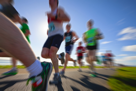 Marathon runners on the bank of ocean bay, blurred motion Stock Photo