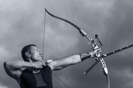 archery: Tough man with bow and arrows, close up with cloudy sky at background. Monochromatic
