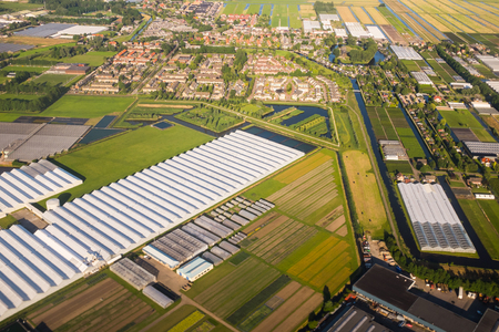 markermeer: Aerial view over the Amsterdam suburbs with canals, houses , fields and greenhouses. Holland