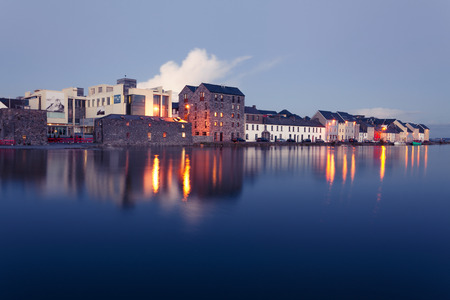 bay city: Buildings on the bank of the river during High tide in the city in dusk. Claddach, Galway, Ireland. Stock Photo