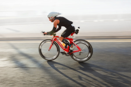 running race: Athlete riding bicycle at sunny day on coastal road, blurred motion