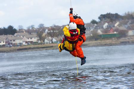 アイルランドの沿岸警備隊の乗組員は海でトレーニング水救助を表示します。