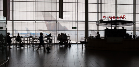 airport window: Airport interior with food bar and tourists.