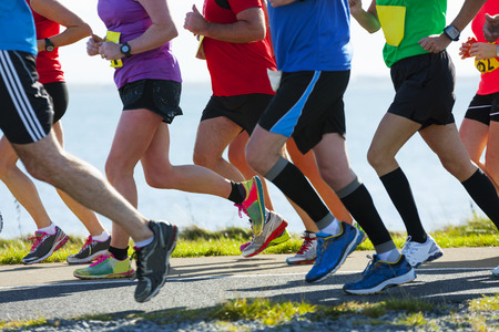 Group of runners compete in the race on coastal road