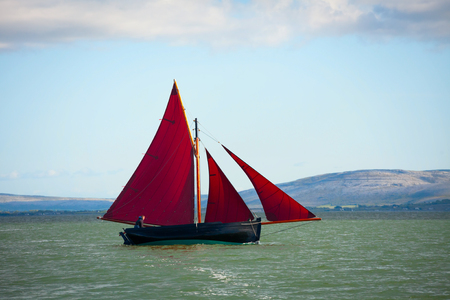 hooker: Traditional wooden boa Galway Hooker, with red sail, compete in regatta. Ireland.