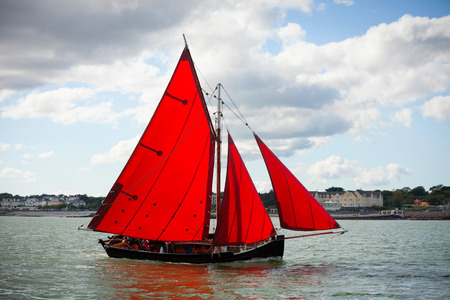 ireland: Traditional wooden boats Galway Hooker, with red sail, compete in regatta. Ireland. Stock Photo