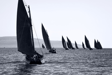 sail: Traditional wooden boats Galway Hooker, with red sail, compete in regatta. Ireland. Stock Photo