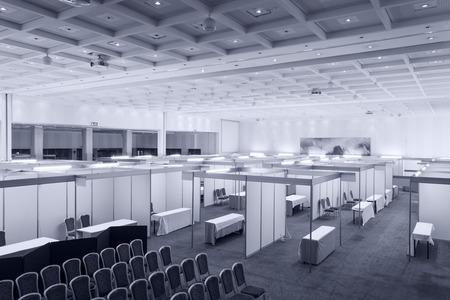 exhibidor: Feria comercial interior con stand y mesas
