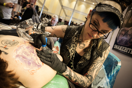 art activity: GALWAY, IRELAND - SEPTEMBER 12: Tattoo Artists at work during The 3rd Annual  International Galway Tattoo Show , on September 12, 2015 in Galway, Ireland. Editorial