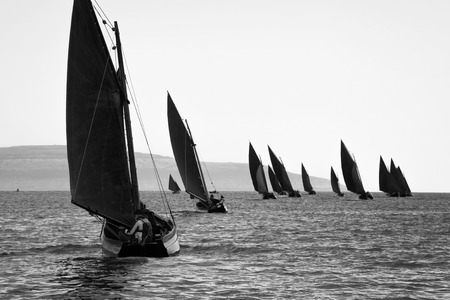 hooker: Traditional wooden boats Galway Hooker, with red sail, compete in regatta. Ireland. Stock Photo