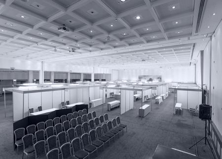expositor: Feria comercial interior con stand y mesas